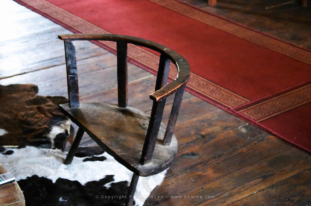 A traditional wooden three legged chair stool. It is the seat of the head of the family. Tradita traditional restaurant, Shkodra. Albania, Balkan, Europe.