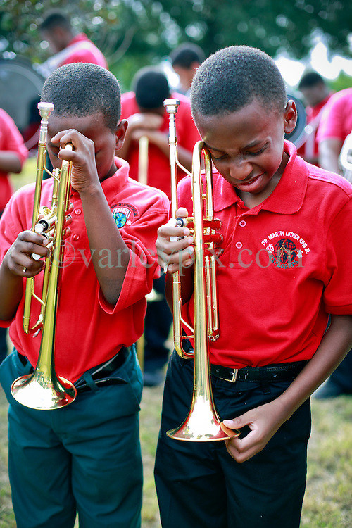 29 August 2014. Lower 9th Ward, New Orleans, Louisiana.<br /> Hurricane Katrina memorial 9 years later. <br /> L/R; Imaad Mays (10 yrs) and Sidney August (11 yrs) from the Martin Luther King Jr Charter High School band say a prayer for victims at the official memorial in remembrance of the day Hurricane Katrina swamped the community.<br /> Photo; Charlie Varley/varleypix.com