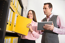 Two young business colleagues working in office