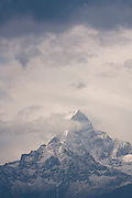 "Clouds surround Machhapuchhre (6993m), or ""Fish Tail"", a sacred peak closed to climbing, as seen from the village of Dhampus along the Annapurna Sanctuary Trek, Himalaya Mountains, Nepal."