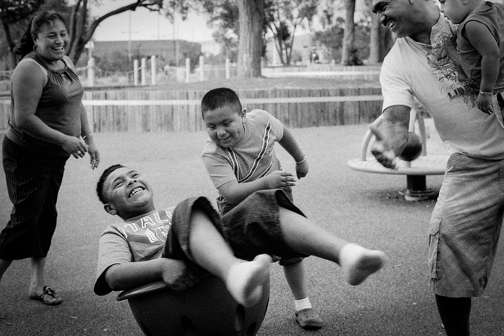 A family has fun spinning in the park.