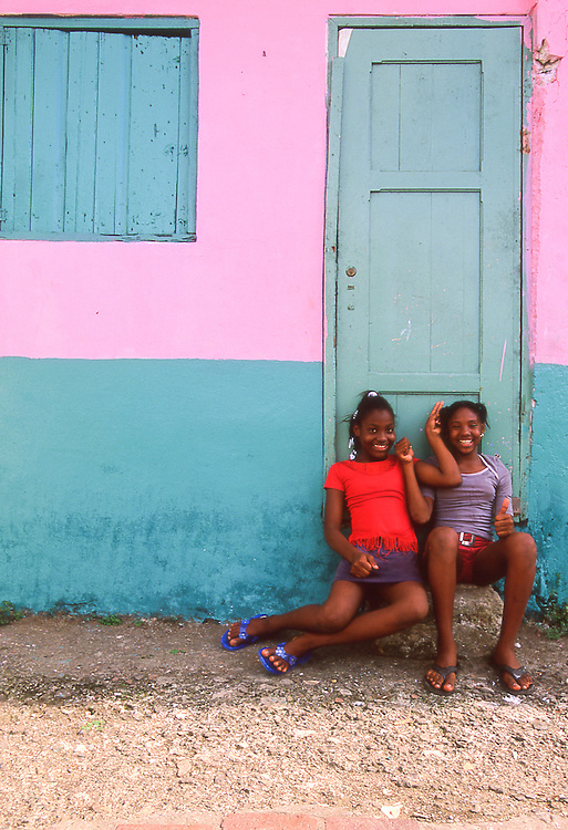 Smiling local girls in the doorway of a colorful entrance to a home in Portobelo, Panama, Central America near Colon Province.