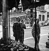 Men walking a street in Chinatown, San Francisco, viewed through storefront window