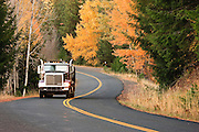A large dumptruck travels a curving backroad through  an autumn forest in rural Klickitat County near Glenwood, WA, USA