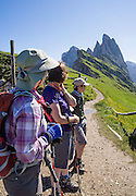 Hikers admire the sharp spires of the Geisler/Odle Group which soar above green Alpe di Seceda, above St. Christina and Ortisei, in South Tyrol, the Dolomites, Italy, Europe. The beautiful ski resort of Selva di Val Gardena (German: Wolkenstein in Gröden; Ladin: Sëlva Gherdëine) makes a great hiking base in the Trentino-Alto Adige/Südtirol (South Tyrol) region of Italy. For our favorite hike in the Dolomiti, start from Selva with the first morning bus to Ortisei, take the Seceda lift, admire great views up at the cross on the edge of Val di Funes (Villnöss), then walk 12 miles (2000 feet up, 5000 feet down) via the steep pass Furcela Forces De Sieles (Forcella Forces de Sielles) to beautiful Vallunga (trail #2 to 16), finishing where you started in Selva. The hike traverses the Geisler/Odle and Puez Groups from verdant pastures to alpine wonders, all preserved in a vast Nature Park: Parco Naturale Puez-Odle (German: Naturpark Puez-Geisler; Ladin: Parch Natural Pöz-Odles). UNESCO honored the Dolomites as a natural World Heritage Site in 2009.