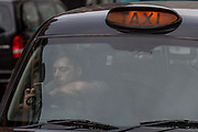 A London cabbie taxi driver checks his windscreen-mounted mobile phone while waiting in a queue for fares outside Liverpool Street mainline station in the City of London - the capitals financial district, on 3rd September 2018, in London England.