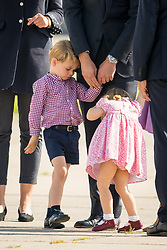 Prince George and Princess Charlotte wait with their parents the Duke and Duchess of Cambridge to board a plane in Hamburg at the end of their visit to Germany.