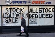An all reduced sale of sports clothing supplier JJB.com stock, being sold by new buyer, Sports Direct shop in central London. A male shopper walks past the store window with a Sports Direct bag, passing the large lettering painted onto the glass, declaring the stock sale. <br /> JJB Sports has collapsed into administration, with arch-rival Sports Direct acquiring 20 stores. KPMG partners Brian Green, David Costley-Wood and Richard Fleming were appointed administrators before Sports Direct bought the JJB assets for £23.77m.