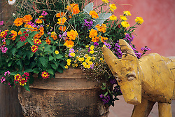 A container with Lantana, Zinnia and other colorful flowers is accented by a pink wall and a folksy carving of a dog in this design by Plant Parenthood of Santa Fe