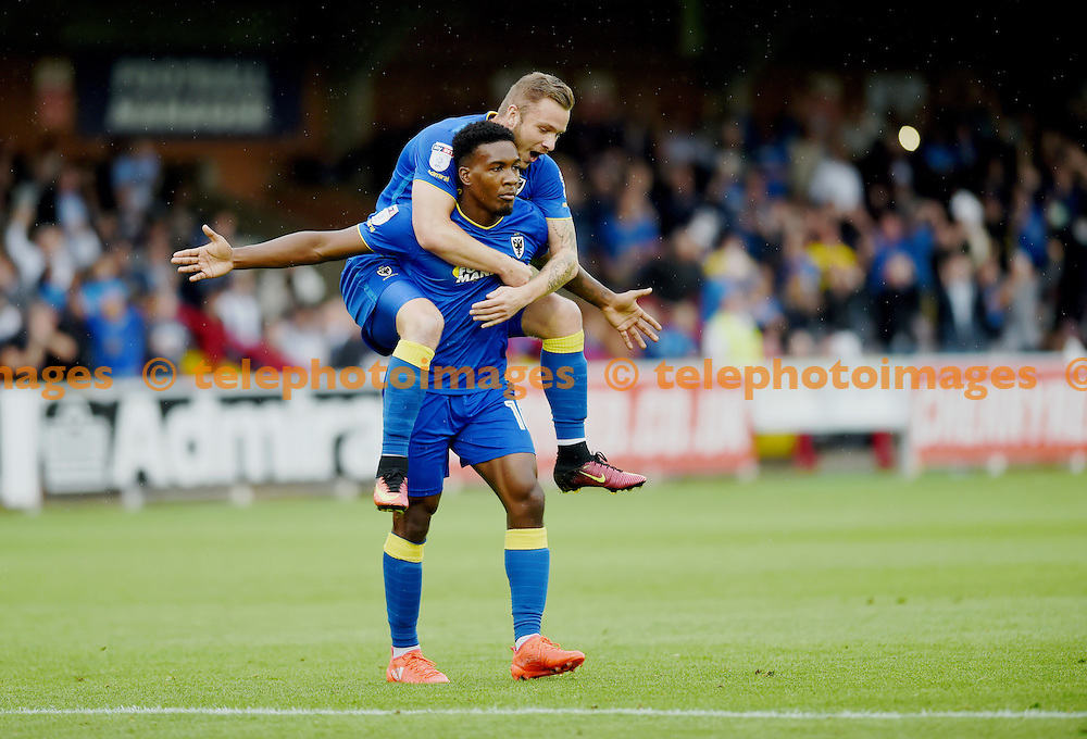 Dominic Poleon of AFC Wimbledon celebrates with Dean Parrett leaping on his back after scoring their late winner during the Sky Bet League 1 match between AFC Wimbledon and Chesterfield at the Cherry Red Records Stadium in Kingston. September 3, 2016.<br /> Simon  Dack / Telephoto Images<br /> +44 7967 642437