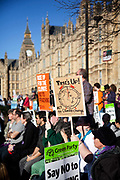A Time's Up placard with Big Ben in the back ground. Demonstrators listen to speeches outside Parliament in the warm spring sun. 20.000 people turned out to the Time to Act  climate demonstration. The demonstration calls for urgent action on climate change and solidarity amongst climate change organisations and social justice groups. The March went peacefully through London to the Houses of Parliament.