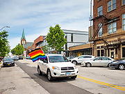 """28 JUNE 2020 - DES MOINES, IOWA: A motorist participates in the Capitol City Pride Parade in Des Moines. Most of the Pride Month events in Des Moines were cancelled this year because of the COVID-19 pandemic, but members of the Des Moines LGBTQI community, and Capitol City Pride, the organization that coordinates Pride Month events, organized a community """"parade"""" of people driving through the East Village of Des Moines displaying gay pride banners and flags. About 75 cars participated in the parade.     PHOTO BY JACK KURTZ"""