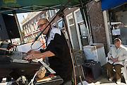 Een man speelt tijdens Koninginnedag muziek op zijn orgels, terwijl zijn vrouw achter hem rustig wacht.<br /> <br /> A man is making music at Queensday, while his wife is waiting besides him.