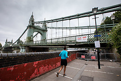 © Licensed to London News Pictures. 14/08/2020. London, UK. A runner goes around Hammersmith Bridge which crosses the River Thames in West London after Fulham Council suddenly closed it to all traffic Thursday night due to safety concerns. Hammersmith Bridge has been close to all traffic including pedestrians, cyclists and boats going under it after cracks in the bridge have become larger by the heatwave. Photo credit: Alex Lentati/LNP