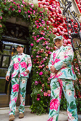 Two doormen in floral suits stand outside Annabels Nightclub. Celebrating the Chelsea Flower Show, after its recent £55 million facelift, Annabel's Nightclub in Berekeley Square, Mayfair, has its entire facade covered in pink and red flowers. London, May 24 2018.