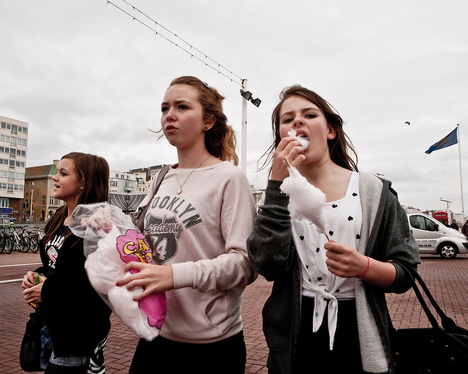 Girlfriends hanging out walking and eating candy floss on the street