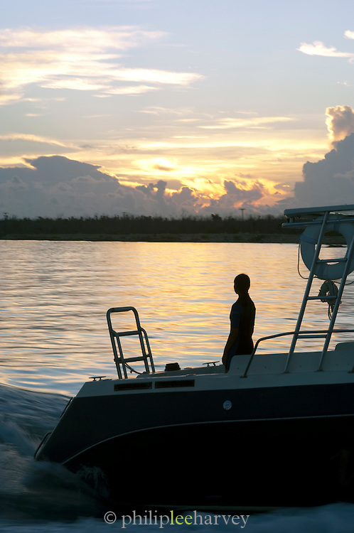 A woman stands at the back of a yacht at sunset in the Caribbean Sea, Mexico