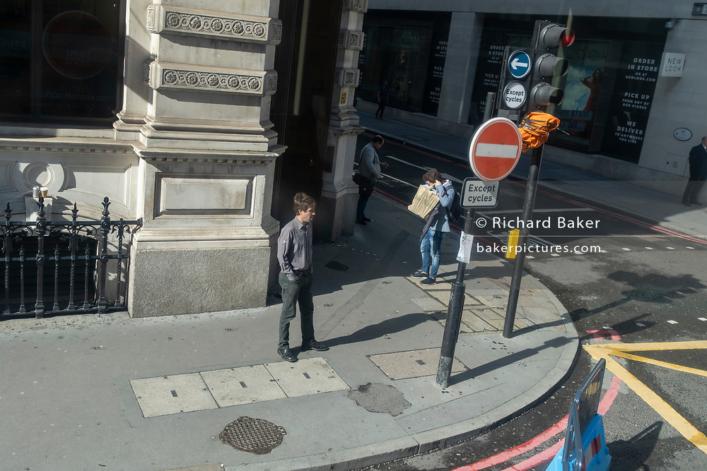 A shopper holding a bag of purchases puts on his face covering on the corner of Lombard Street and Bishopsgate in the City of London, the capital's financial district, and during the second (Autumn) spike Coronavirus pandemic, on 5th October 2020, in London, England.