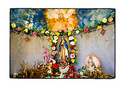 SHOT 2/19/19 10:16:07 AM - The inside of a small capilla on the main square in Castamay along Highway 261 in the state of Campeche Mexico. The capitlla featured a statue of Nuestra Señora de Guadalupe as well as flowers and a painting of Jesus. Our Lady of Guadalupe is a powerful and ubiquitous symbol of Mexican identity because some guess that Our Lady of Guadalupe's skin tone matches that of Mexico's indigenous population: light brown. She is as much revered for her striking similarity to the vanquished native Mexican population as she is for being the mother of God. The capillas are often dedicated to certain patron saints or the memory of someone that has died at or near the site. Common throughout the backroads and secondary highways of Mexico they often contain prayer candles, pictures, personal artifacts or handwritten notes. (Photo by Marc Piscotty / © 2019)
