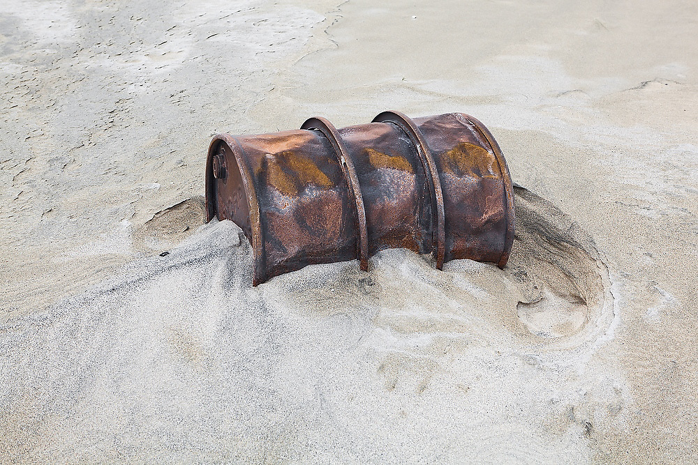 A rusted steel drum washed up on the sand at Horseid Beach, Moskenesoya, Lofoten Islands, Norway.