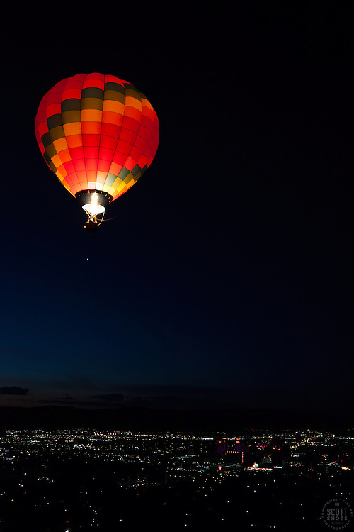 """""""Dawn Patrol 11"""" - Photograph of a glowing hot air balloon flying for the Dawn Patrol at the 2012 Great Reno Balloon Race. Photographed from a hot air balloon."""