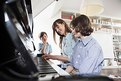 Mother and daughter playing piano while brother listening
