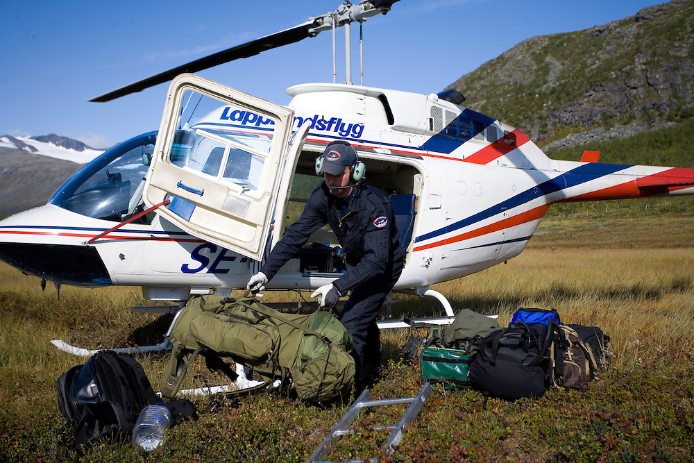 Helicopter pilot unloading equipment for WWE filming mission, Sarek National Park, Laponia World Heritage Site, Sweden