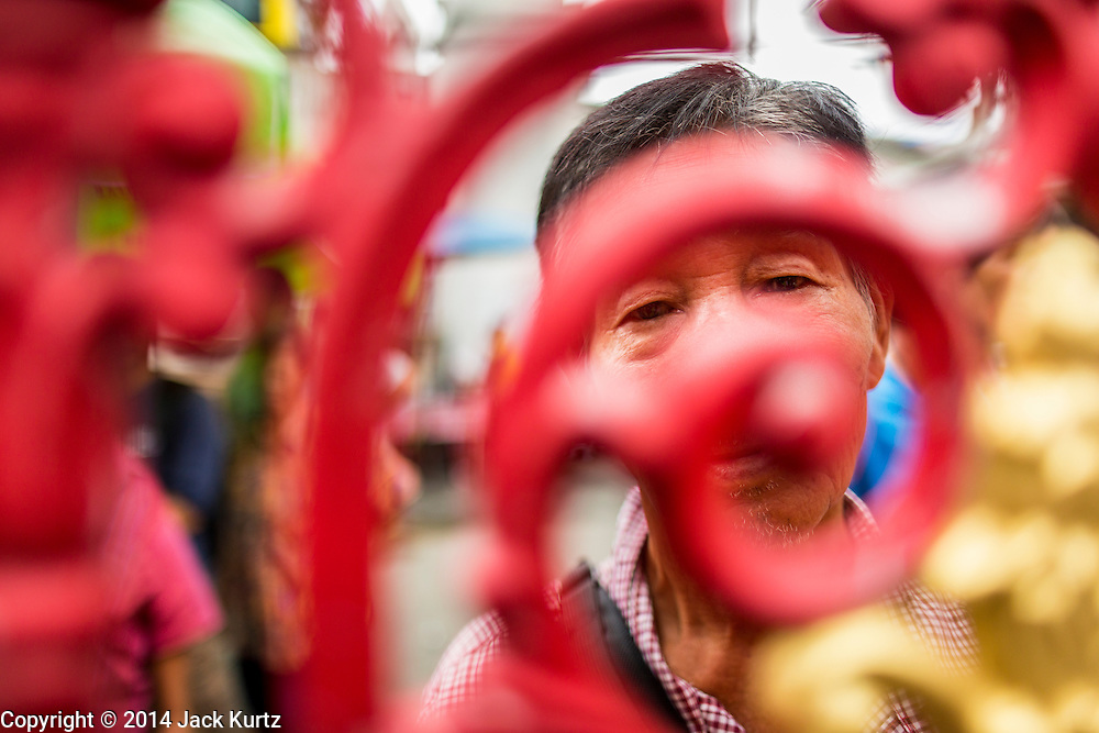 """09 AUGUST 2014 - BANGKOK, THAILAND: People wait to get into the Ruby Goddess Shrine in the Dusit section of Bangkok for a Ghost Month food distribution. The seventh month of the Chinese Lunar calendar is called """"Ghost Month"""" during which ghosts and spirits, including those of the deceased ancestors, come out from the lower realm. It is common for Chinese people to make merit during the month by burning """"hell money"""" and presenting food to the ghosts. At Chinese temples in Thailand, it is also customary to give food to the poorer people in the community.         PHOTO BY JACK KURTZ"""