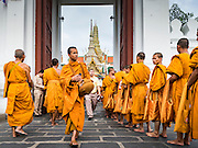 09 JUNE 2016 - BANGKOK, THAILAND: Buddhist monks walk into Wat Phra Kaew on the grounds of the Grand Palace after an alms giving ceremony at the Grand Palace Thursday. Thailand marked 70 years of the reign of Bhumibol Adulyadej with a special alms giving ceremony for 770 monks in front of the Grand Palace in Bangkok. The King, also known as Rama IX, ascended the throne on 9 June 1946. He is the longest serving monarch in Thai history and the longest serving monarch in the world today. He is revered by most Thais and is widely seen as a unifying figure in the country.     PHOTO BY JACK KURTZ
