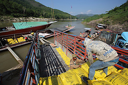 Labourers work to unload a Cargo river boat carrying fertilizer on the River Mekong.  Pak Beng, Oudomxay Province, Lao PDR