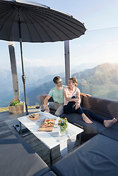Couple relaxing on sofa on terrace, Zillertal, Tyrol, Austria