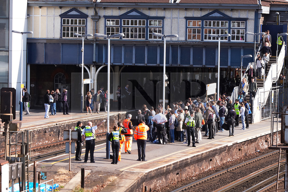 © licensed to London News Pictures. LONDON, UK  04/05/2011. Police and rail staff keep Clapham Junction commuters away from where a person was hit by a train at about 7:30am this morning. The incident caused significant disruption at the height of rush hour. Police are treating the death as not suspicious. Please see special instructions for usage rates. Photo credit should read CLIFF HIDE/LNP