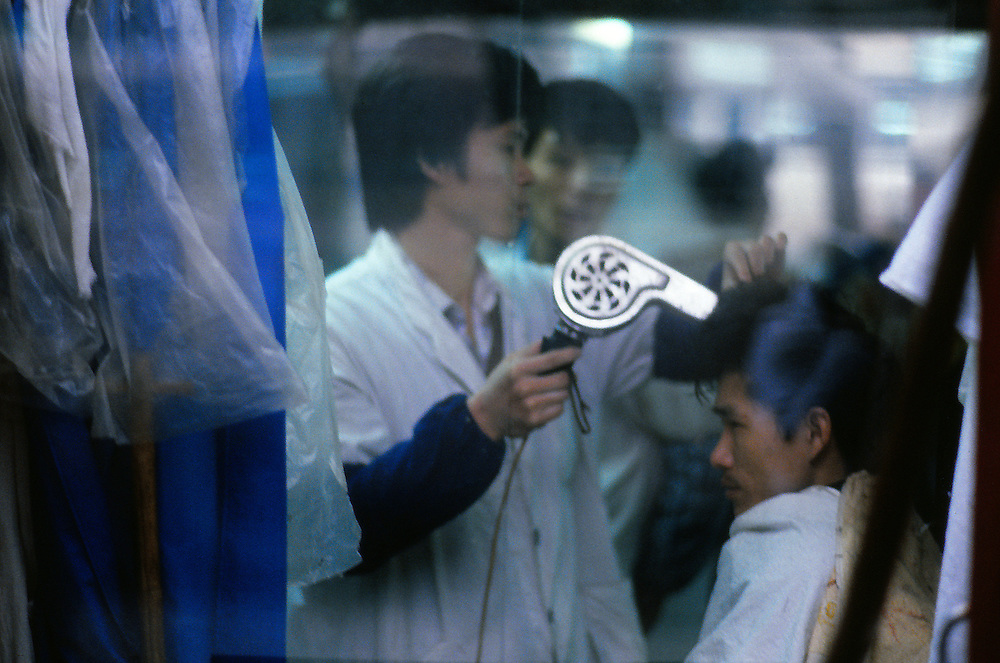 In the quiet and rainy Beijing of the eighties, the hairdresser's window shop remains the ambiance of Blade Runner...
