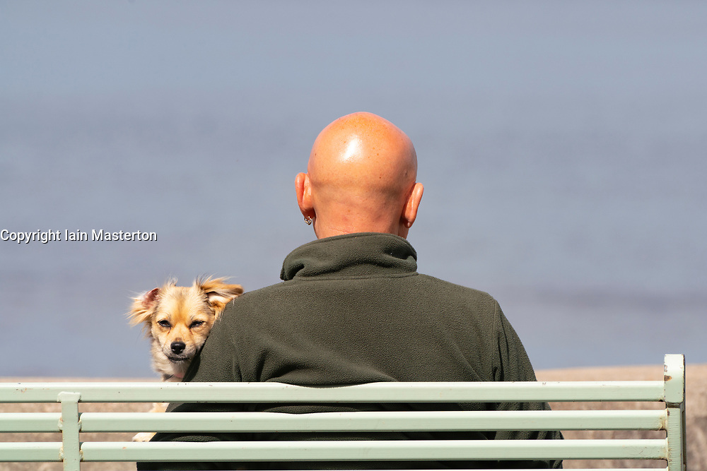 Portobello, Scotland, UK. 11 May 2020. Late afternoon views of popular Portobello beach and promenade. Despite occasional police patrols, the public were determined to relax and enjoy sitting in the sunshine. Man and dog enjoy sitting in the sun. Iain Masterton/Alamy Live News