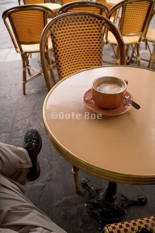 man alone sitting at a sidewalk cafe in Paris