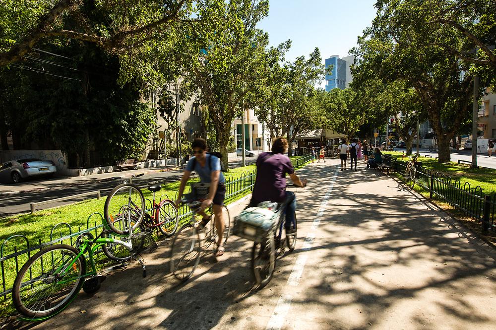 People ride their bicycles on Rothschild Boulevard in Tel Aviv's Lev Hair neighborhood