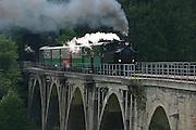 A steam hauled tourist train of the Feistritztalbahn slowly crosses the 276m long Grub-Viadukt while passengers watch and take souvenir photos.