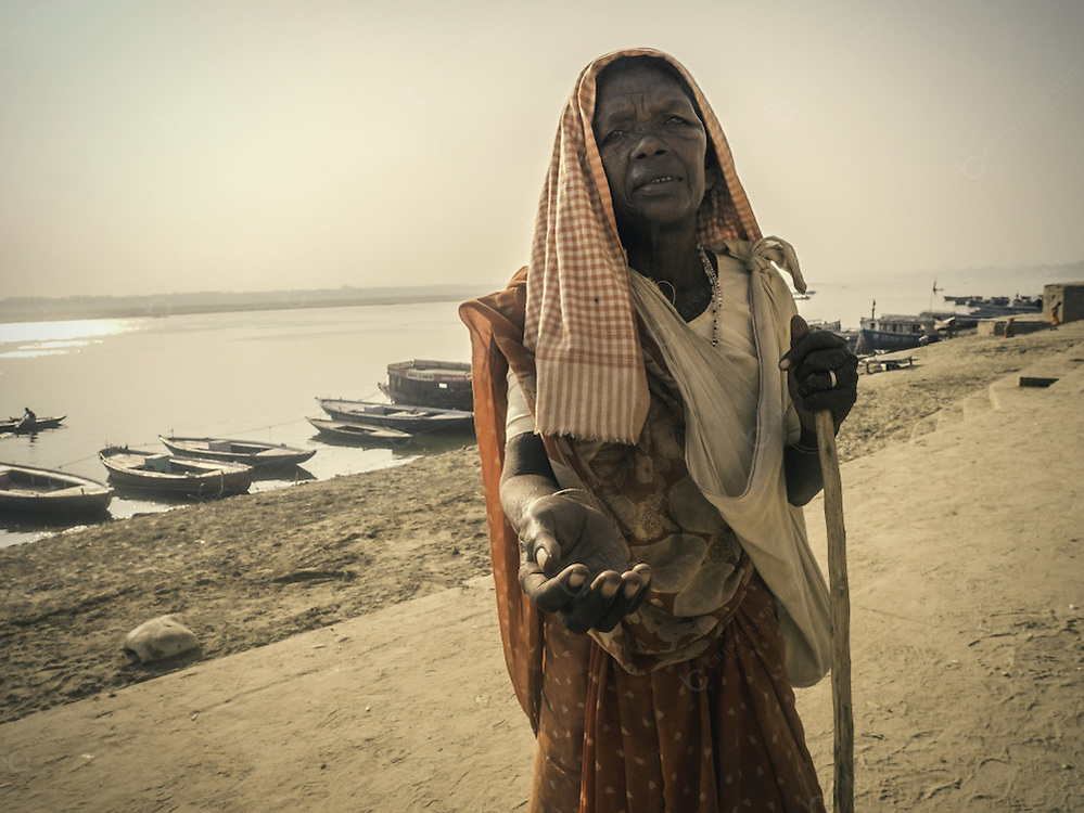 Varanasi, India - October 09, 2015 Woman begging in the ghats of Varanasi India. Poverty is very present in the city specially among senior women. Thousands of poor widows end in the city as they believe if they die here they will be released by the cycle of reincarnation and attain Moksha.