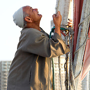 Felucca sailor attends to the sail on his boat on the River Nile in Cairo, Egypt.