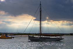An oyster smack lies at anchor under a brooding sky over the Blackwater Estuary, famous for its oysters, at West Mersea, Mersea Island, near Colchester in Essex. West Mersea, Essex, July 10 2019.
