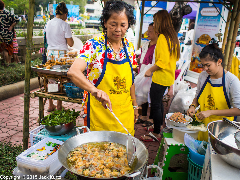 """12 FEBRUARY 2015 - BANGKOK, THAILAND:  A vendor makes deep fries Thai snacks called """"toong tong"""" or money bags, in her stand on Khlong Phadung Krung Kasem, a 5.5 kilometre long canal dug as a moat around Bangkok in the 1850s. The floating market opened at the north end of the canal near Government House, which is the office of the Prime Minister. The floating market was the idea of Thai Prime Minister General Prayuth Chan-ocha. The market will be open until March 1.   PHOTO BY JACK KURTZ"""