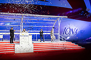 """Britain's largest and most environmentally-friendly cruise ship is named in a record-breaking virtual ceremony.<br /> <br /> A Nebuchadnezzar of Alex James's Britpop cider smashes onto the side of P&O Cruises Iona at the ships' naming ceremony in Southampton tonight.<br /> <br /> Britain's largest and most environmentally-friendly cruise ship, P&O Cruises Iona, has been officially named in a very contemporary ceremony with a record-breaking virtual audience.<br /> <br /> Iona, powered by liquefied natural gas, ground-breaking for the UK cruise industry and one of the cleanest fuels in the world, arrived for the first time into her home port of Southampton this morning ahead of tonight's official naming ceremony.<br /> <br /> The ship was officially named tonight by Dame Irene Hays, chair of Hays Travel (second from left), Britain's largest independent travel agency, in a glittering quayside ceremony by the bow of the ship. <br /> <br /> The event, held at sunset, was hosted by Jo Whiley (right) and broadcast to a """"virtual"""" audience of over 25,000 guests. The highlight of the show was a rousing set from Iona's music director Gary Barlow performing two iconic Take That hits """"Greatest Day and """"Rule the World"""" against the backdrop of a spectacular laser show.<br /> <br /> A specially produced Nebuchadnezzar (equivalent to 20x 750ml bottles) of Alex James's Britpop cider smashed against the hull of the ship in spectacular style to bring it good fortune in the future.  <br /> <br /> There was also a special performance by The Commonwealth Youth Orchestra and Choir and Mica Paris singing Believe, a song which was composed by Simon Haw MBE and was dedicated to Her Majesty The Queen, head of the Commonwealth, for its 70th anniversary in 2019.<br /> <br /> Also pictured is the master of the ship, Captain Wesley Dunlop and Paul Ludlow, President of P&O Cruises.<br /> <br /> Picture date Sunday 16th May, 2021.<br /> Picture by Christopher Ison. Contact +447544 044177 chris@chri"""