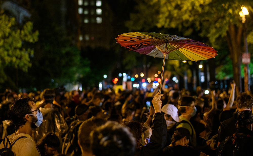 People weather the thunderstorm to continue protesting the killing of George Floyd in police custody, at Lafayette Square Park, in Washington DC. Police had installed a double fence to prevent the crowd from advancing into the park.