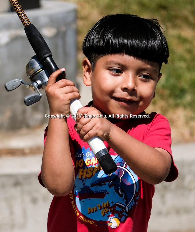 5月13日,孩子专心钓鱼。当日,在美国加利福尼亚州洛杉矶,洛杉矶市康乐与公园局在市中心附近的麦克阿瑟公园举办免费青少年儿童钓鱼日活动。所有15岁以下的孩子,都可得到免费的钓鱼训练、鱼竿与鱼饵。新华社发 (赵汉荣摄)<br /> A boy fishes during a youth fishing derby held by the Los Angeles Department of Recreation and Parks, in the lake at MacArthur Park near downtown Los Angeles, the United States on May 13, 2017. (Xinhua/Zhao Hanrong)(Photo by Ringo Chiu/PHOTOFORMULA.com)<br /> <br /> Usage Notes: This content is intended for editorial use only. For other uses, additional clearances may be required.