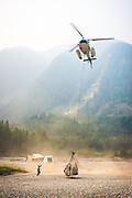 David Higman uses his cell phone to video a helicopter sling load of camping gear. Dean River, BC