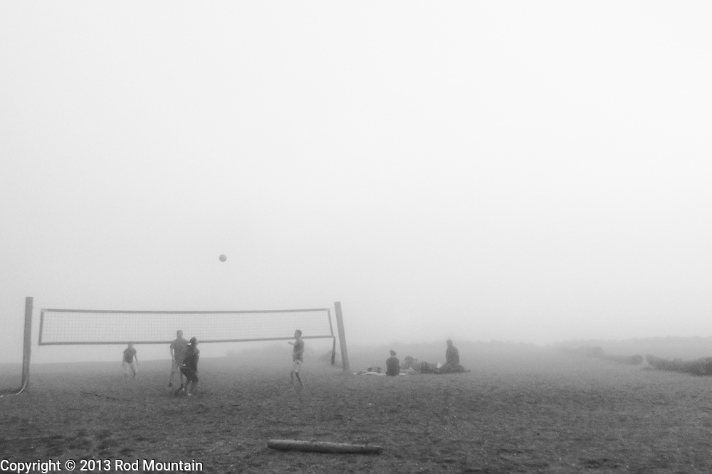 A group of young men play a casual game of volleyball during a foggy day at Kitsilano Beach in Vancouver, BC. <br /> <br /> Photo: © Rod Mountain<br /> <br /> http://www.rodmountain.com