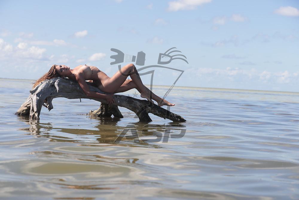 A hispanic nude brunette model enjoying the beach
