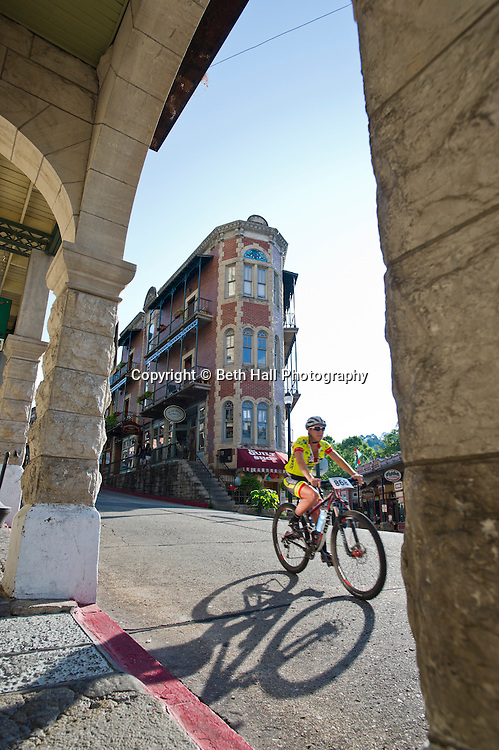 Stock photography of a biker riding through downtown before the Fat Tire Festival in Eureka Springs, Arkansas.