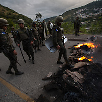 Honduran Army begin to move a burning barricade on the outskirts of the capital Tegucigalpa.