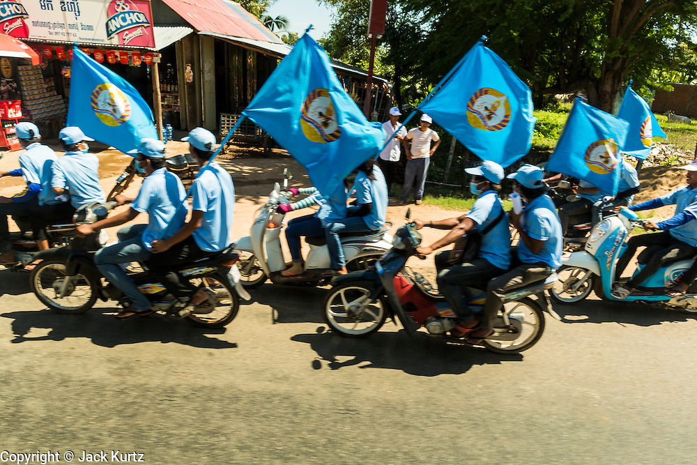 29 JUNE 2013 - CAMBODIA:  People on motorcycles campaign for the Cambodia People's Party in rural Cambodia. The CPP, party of long serving Prime Minister Hun Sen, is expected to win the election, which is scheduled for July 28.    PHOTO BY JACK KURTZ